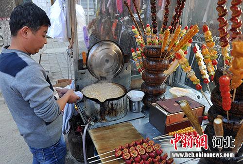 庙会上,有一个卖糖墩儿的摊位十分受欢迎,时不时还会有老年人光顾。 韩冰 摄