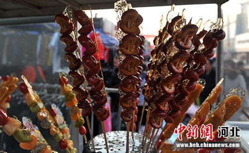 """糖墩儿,是将红果、海棠、山药段,用竹签穿成串儿,外蘸冰花糖汁,北京叫""""大冰糖葫芦""""。 韩冰 摄"""