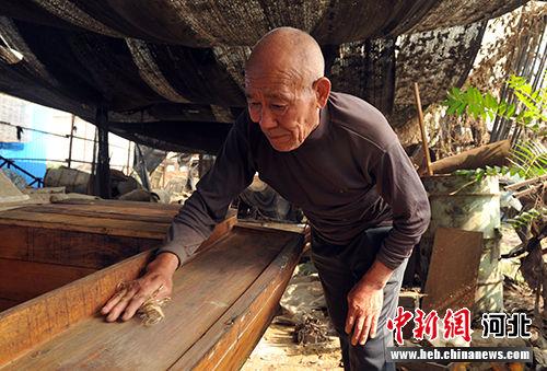 姜琳祥在造船大棚里擦拭所造的木船。 韩冰 摄