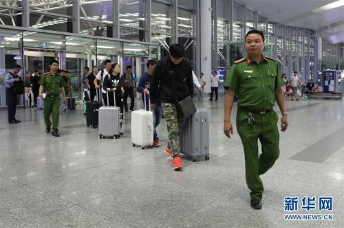 """4月28日,嫌疑人在中越警方押送下进入越南河内内排国际机场。当日,越南警方在河内内排国际机场向中国警方工作组移交了许某等8名涉嫌诈骗罪的在逃嫌疑人。中国警方""""猎狐行动""""在越南再获新成果。新华社记者 王迪 摄 图片来源:新华网"""