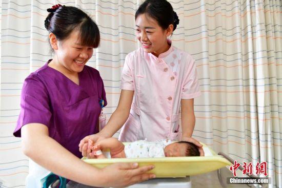 """5月10日,河北石家庄市妇产医院,河北一大学的大一新生韩荣荣(粉色)在护士的指导下为新生儿称体重。""""5.12国际护士节""""到来之际,该院举办""""护士体验日""""相关活动。体验当日,""""95后""""大学生们穿梭在病房与手术室,了解真正的""""白衣天使"""",体味她们工作中的酸甜苦辣。中新社记者 翟羽佳 摄"""