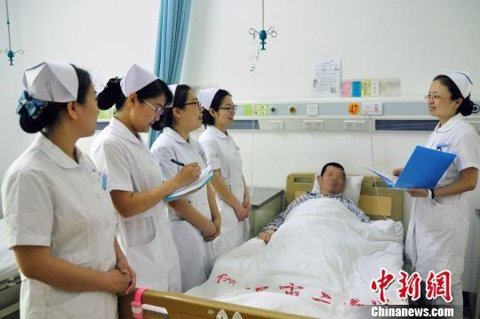护士长徐慧(右)带领护士查房。 刘丽娟 摄