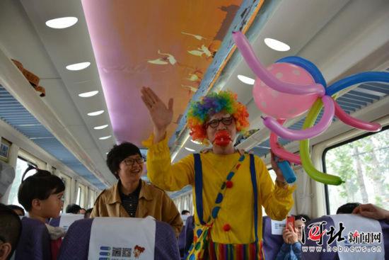 """5月15日,""""秦旅山海号""""旅游小火车开始试运行。图为旅游小火车上,小丑与乘客互动。记者杨琦摄"""