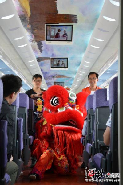 """5月15日,""""秦旅山海号""""旅游小火车开始试运行。图为旅游小火车上的舞狮表演。记者杨琦摄"""