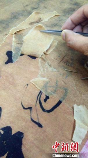 郝化彬对破损残缺书画进行装裱修复工作。 孙瑞超 摄