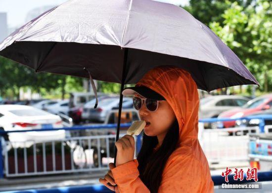 6月5日中午,河北石家庄户外温度达到38℃,市民们出行时携带各种遮阳护具。受暖气团影响,今日,该省多地最高气温可达36℃至38℃,其中中南部局地可达39℃至40℃。 中新社记者 翟羽佳 摄