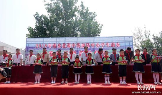 与会领导向学生发放《中小学生防溺水作业本》 记者 张欣 摄