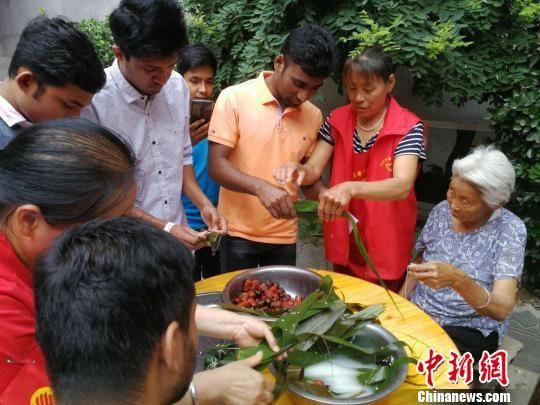 孟加拉国留学生学习包粽子。 李晓伟 摄