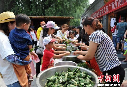 文化苑工作人员摆好包粽子的苇叶、糯米等,和游客一同包粽子。 韩冰 摄
