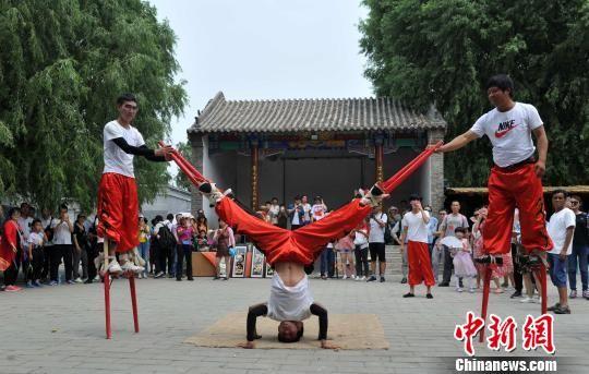 文化苑广场内,高跷会的表演者正在表演倒立。 韩冰 摄