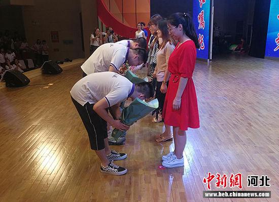 毕业生们为培养了自己三年的老师送上鲜花并鞠躬致谢。 王鹏 摄
