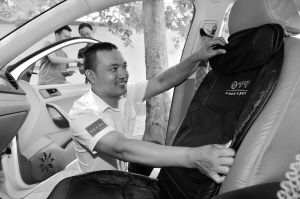 """近日,石家庄部分出租车开始试装""""车载共享按摩垫"""",市民在乘坐出租车出行时不仅快捷方便,还能享受到温馨的按摩服务。目前,我市出租车已安装80台。图为出租车司机在调试按摩垫。本报记者 张晓峰 摄"""