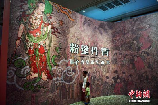 """8月2日,由河北博物院、石家庄市毗卢寺博物院主办的""""粉壁丹青――毗卢寺壁画艺术展""""在河北博物院举行。展区的毗卢殿四壁120余平方米的中国传统水陆道场画吸引了众多参观者,工整的构图、精湛的技艺以及丰富的内涵,展现了明代壁画的精美。据记载,毗卢寺于宋、金、元、明、清时期均经修葺完善,寺内壁画也承载了历代壁画的特点以及画师高超的技艺。图为两名小孩被精美的壁画艺术展吸引。中新社记者 翟羽佳 摄"""