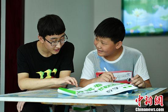 图为暑假期间,已是大学生的秦敬博(左)经常辅导同村孩童功课。(资料图片) 中新社记者 翟羽佳 摄