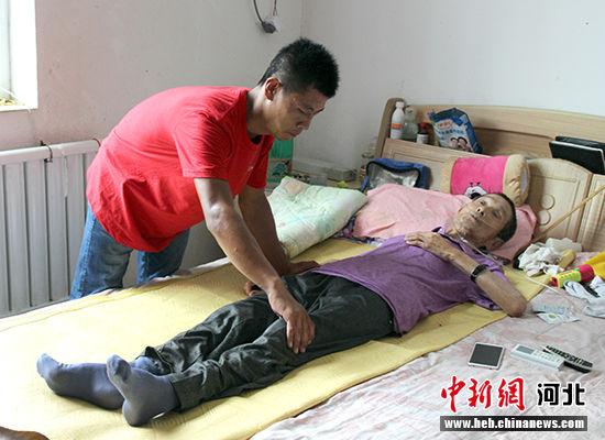 在敬老院工作的杨朝阳在热情地为老人做按摩。赵庆斌摄