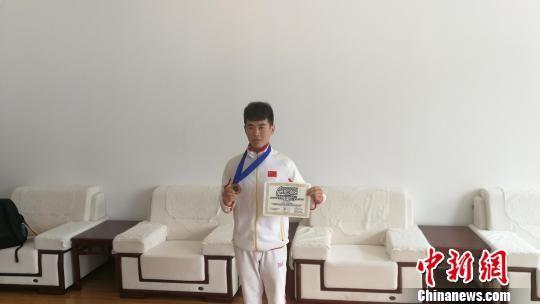 曹安蚺展示奖牌和证书。 王鹏 摄