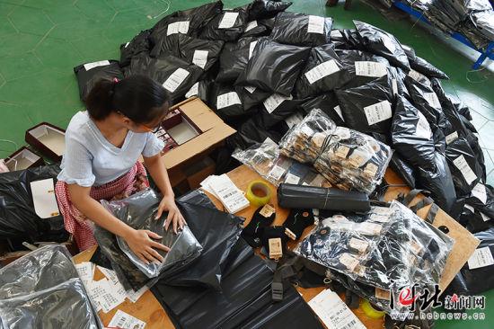 8月23日,无极县王吕村一村民家中,范敬巧麻利地装袋打包,身旁堆满了待发的快件。王吕村曾是有名的皮革村,随着环保压力不断加大,该村开始转型为以童装销售为主导的电商村,从2011年的两三户发展到现在的200多户,解决本村及周边村镇700余人就业,年销售额超5亿元。 记者赵海江 通讯员甄建坡摄影报道