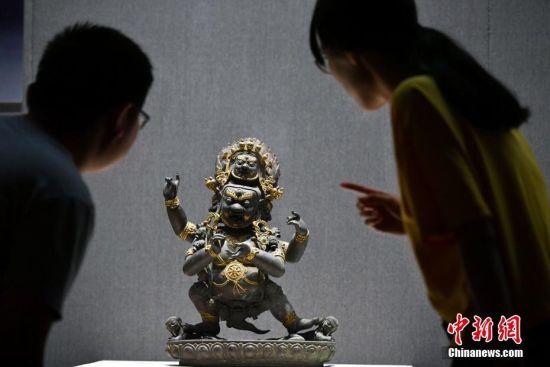 """9月4日,《菩提华光――河北博物院藏铜佛造像展》在河北石家庄开展。此次约有200余尊十六国至清代的精品铜佛造像对外展出,让民众简单了解佛教及佛像之演变,并欣赏其艺术之美。图为观众参观罕见的清代""""四臂大黑天""""铜佛造像。中新社记者 翟羽佳 摄"""