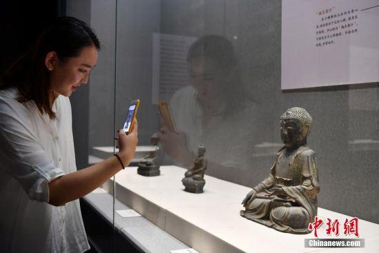9月4日,《菩提华光――河北博物院藏铜佛造像展》在河北石家庄开展。此次约有200余尊十六国至清代的精品铜佛造像对外展出,让民众简单了解佛教及佛像之演变,并欣赏其艺术之美。图为一名观众用手机拍摄展品。中新社记者 翟羽佳 摄