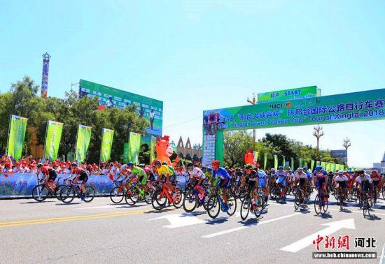 """发令枪响,2018""""邢台大峡谷杯""""环邢台国际公路自行车赛第二赛段选手迅速冲出起点。 张驰 摄"""
