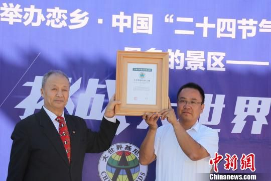"""上海大世界基尼斯总部理事会理事刘安胜(左)向易县""""恋乡?太行水镇""""景区负责人颁发证书。 于俊亮 摄"""
