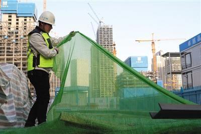 今年2月,中国铁物大厦项目工地配备网眼更细密的防尘网,有助更好控制扬尘污染。 资料图片/新京报记者 吴江 摄