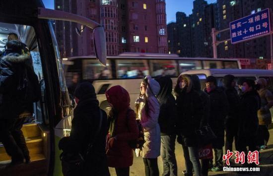 资料图:河北燕郊开往北京大望路的公交车下,上班族在寒风中排队上车。 中新社记者 张浩 摄