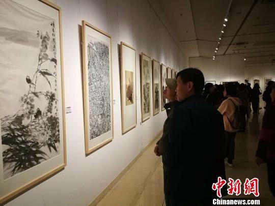 观众正在欣赏参与展出的画作。 李晓伟 摄