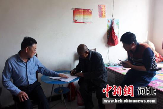 图为固安县脱贫帮扶人员在贫苦户家里耐心讲解帮扶政策。 刘文波 摄