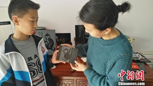 图为方士英在看儿子创作的生肖作品,后面桌子上的生肖图案为方士英创作。 陈林 摄