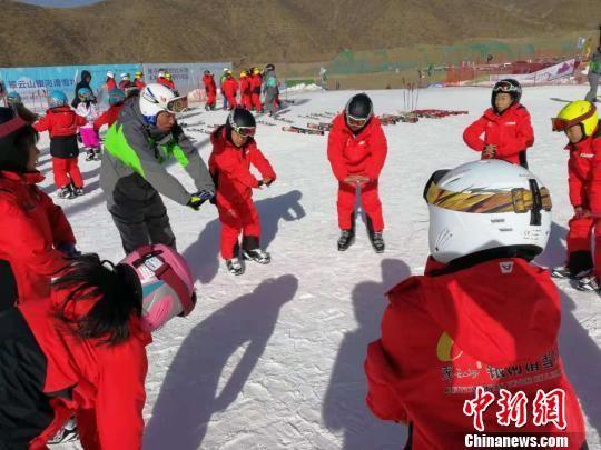 图为专业教练教授孩子们滑雪基础动作。 王春亮 摄