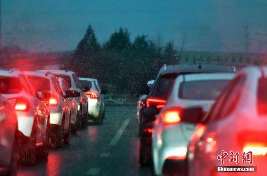 12月5日,河北石家庄,降雪天气影响市民出行。据了解,受较强冷空气影响,今日起未来三天,该省各地最低气温将明显下降,降温幅度普遍在6~8℃之间,其中北部地区局地可达8~12℃。图为降雪导致车辆缓慢行驶。