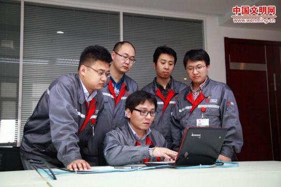 郭鹞(中)正在和团队成员讨论产品图样。图片由河北省文明办提供