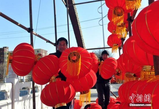 图为雄安新区安新街头民众们在挂灯笼。 中新社记者 韩冰 摄