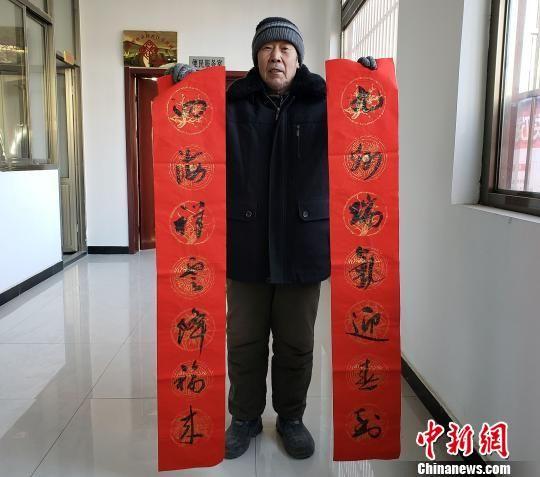 75岁的村民李英展示书法家为他写的春联。 徐巧明 摄