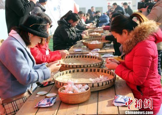 1月13日,正值中国传统节日腊八节,图为游客正在进行剥蒜比赛。 徐巧明 摄