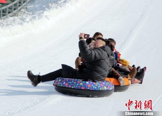 游客体验滑雪圈运动并自拍。 徐巧明 摄