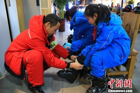 图为专业教练帮助孩子们穿上滑雪鞋。 李云龙 摄