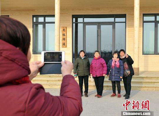 """图为村民在""""秀林驿站""""前合影。中新社记者 韩冰 摄"""