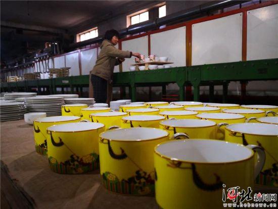 图为工人正在进行贴花作业。 记者王育民摄