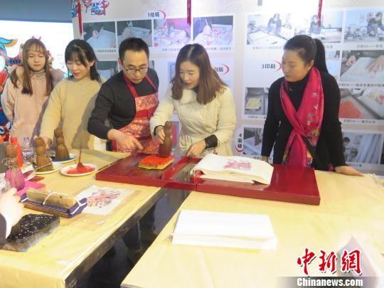 武强年画博物馆工艺师刘兵指导观众体验武强年画《生肖猪》套色印刷。武强年画博物馆供图