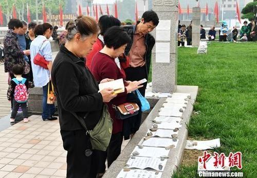 资料图:河北石家庄相亲广场,父母正在帮孩子看征婚信息。中新社记者 翟羽佳 摄