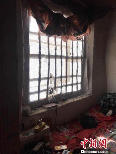 图为梁三片家,窗户上的洞是为了方便猫咪出去抓老鼠。到了睡觉的时候,他用窗帘把窗户封严。 张帆 摄