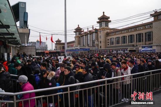 资料图:旅客们在北京站前排队进入地铁。中新社记者 崔楠 摄