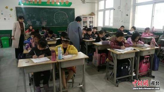 育才小学的志愿者教师在对学生进行课后无偿辅导。 李铁锤 摄