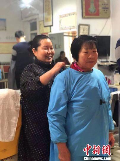 郭燕的母亲今年70岁,老人手艺未丢,依旧剃头理发。郭燕(左)帮母亲整理衣服。 李铁锤 摄