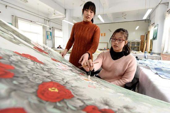 3月12日,李娜在母亲陪伴下绘制工笔画。 新华社记者朱旭东摄