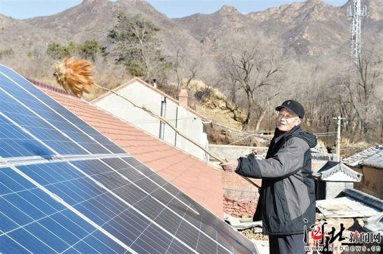"""承德县76岁的刘少信老人在自家屋顶上清扫太阳能发电板。该县利用天津对口帮扶资金大力实施""""万户阳光工程"""",带动626户贫困户年均增收3000元。(资料片) 记者赵海江摄"""