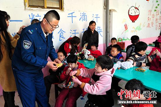 爱心人士把带来的水果和小食品分给孩子们。 郭云民 摄