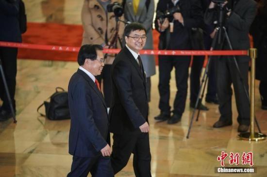 """3月5日,十三届全国人大二次会议在北京人民大会堂开幕。图为全国人大代表李东生(左)、陈刚(右)步入""""代表通道""""接受采访。中新社记者 崔楠 摄"""